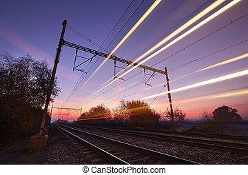Train at the sunrise - Passenger train on railroad tracks at...