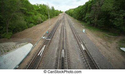 Train enters under bridge in forest - train enters under...