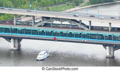 Train goes on Luzhnetsky bridge and stops on metro station Mountains Vorobevy