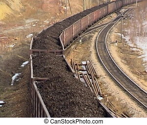 Train in motion. - Coal wagons on railway tracks.