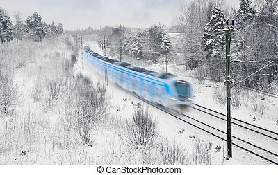 Train in snow - Blue and white commuter train in blurred ...