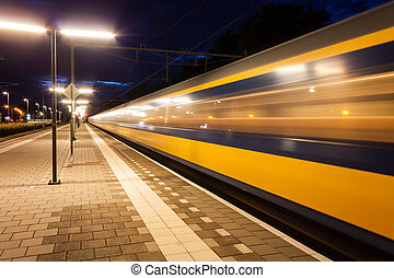 Train leaving train station - Yellow and blue train leaving...