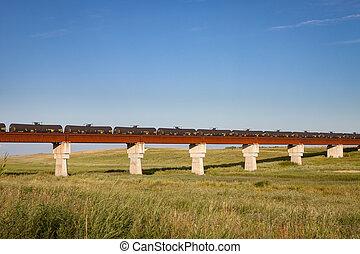 Train of Black Tank Cars Crossing a Rusty Bridge