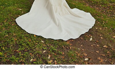 Train of wedding dress of bride on grass. Close-up. Wedding day.
