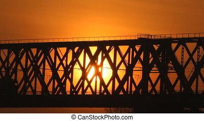 Train on the bridge at sunset. Rail