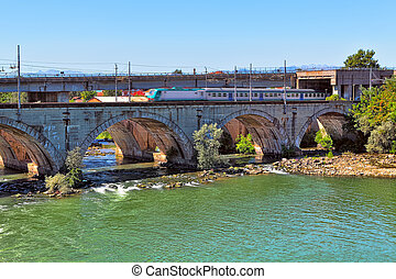 Train on the bridge over the river in Piedmont, Italy.