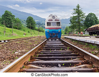 Train on the railroad tracks on railway station in Carpathians