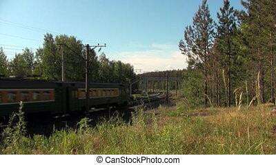 train passes under a footbridge