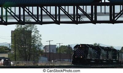 Train passes under a pedestrian/biking bridge