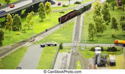 train pushes freight cars on rail in modern toy city among roads and trees