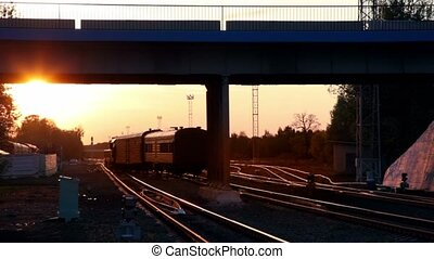 Train ride under bridge with car passes by at background of...