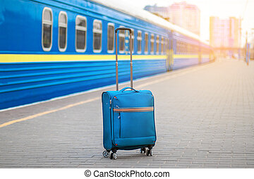 Train station and suitcase on the platform. Travel and vacation concept. Empty platform, epidemic, suspension of railway traffic