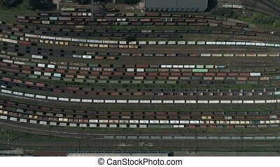 Train station with freight trains and containers in aerial view. Aerial shooting top down footage of railway transportation hub showing the different trains parked, 4k