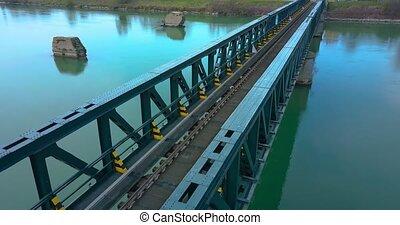 Train tracks cross a steel bridge over the river