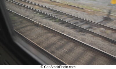 Looking through train window at railroad tracks below. Several tracks merge into a single track, and then an additional track veers off at switch point.