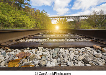 Train tracks with a bridge in the background, train tracks in a rural scene with a nice pastel sunset