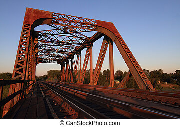 A view of a steel train trestle at sunset