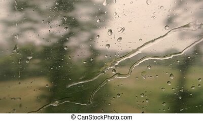 Train window with water droplets. Blurred landscape and sky....