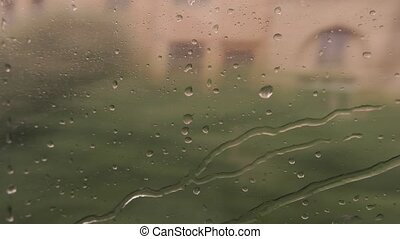Train window with water drops. Blurred landscape at daytime....