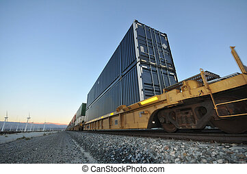 Train with stacked containers rolls by windfarm - Train with...
