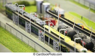 train with tank goes by rail from fuel station in modern toy city