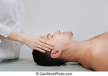 Trained skillful doctor conducting a therapeutic relaxing procedure