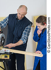Trainee carpenter watching how to use circular saw