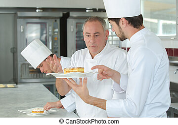 Trainee chef talking to his superior