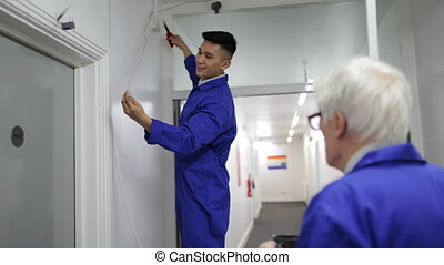 Trainee electrician is fitting a security camera with assistance from his tutor.