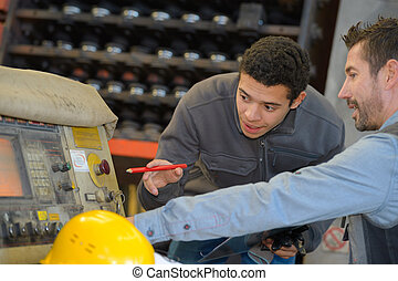 trainee learning how to use a machine at the factory