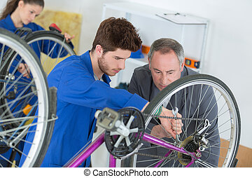 Trainee mechanic repairing bicycle