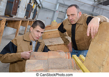 trainee roofer learning how to tile a roof properly