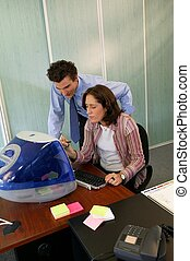 Trainee with manager in front of desktop computer