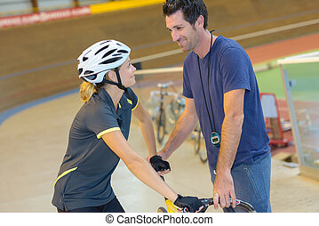 Trainer and cyclist talking over bicycle