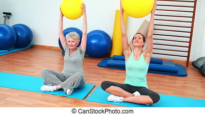 Trainer and elderly client raising exercise balls at the...