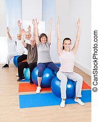 Trainer And Senior Customers Stretching On Fitness Balls -...