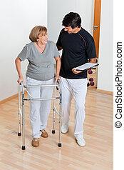 trainer, anschauen, ältere frau, gebrauchend, gehhilfe