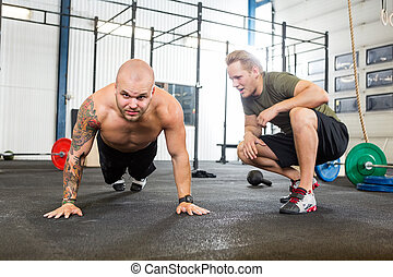 Trainer Assisting Man In Doing Pushups