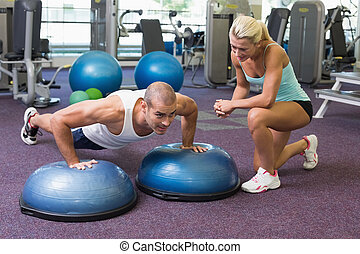 Trainer assisting man with push up