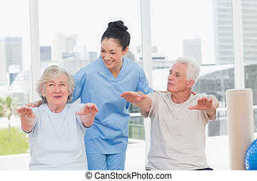 Trainer assisting senior couple to exercise - Happy trainer...