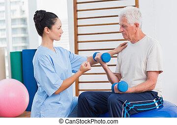 Trainer assisting senior man in lifting dumbbells
