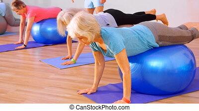 Trainer assisting senior women in performing yoga 4k - ...
