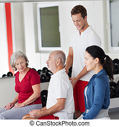 Trainer correcting the posture of an elderly man