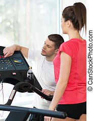 Trainer explains to a young woman how to use treadmill in fitness club