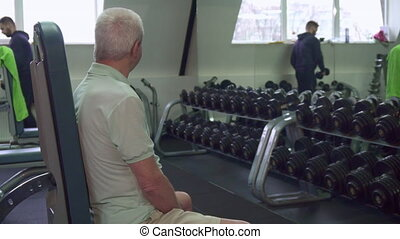 Young caucasian trainer giving dumbbells to the senior client. Old gray man sitting on fitness bench at the gym. Aged male sportsman prepare for exercises