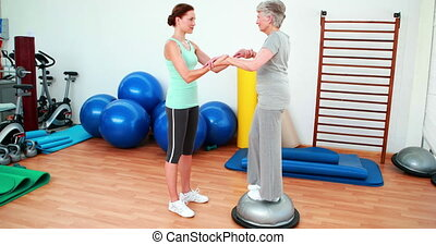 Trainer helping elderly client to use bosu ball at the...