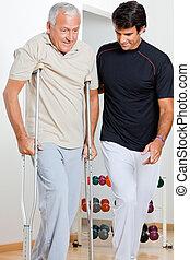 Trainer Helping Senior Man To Walk