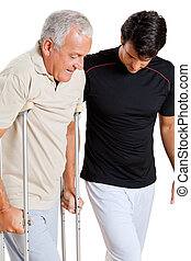 Trainer Helping Senior Man With Crutches - Trainer helping...