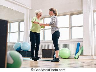Trainer helping senior woman on bosu balance training platform