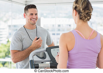 Trainer helping woman on treadmill - Physical trainer...